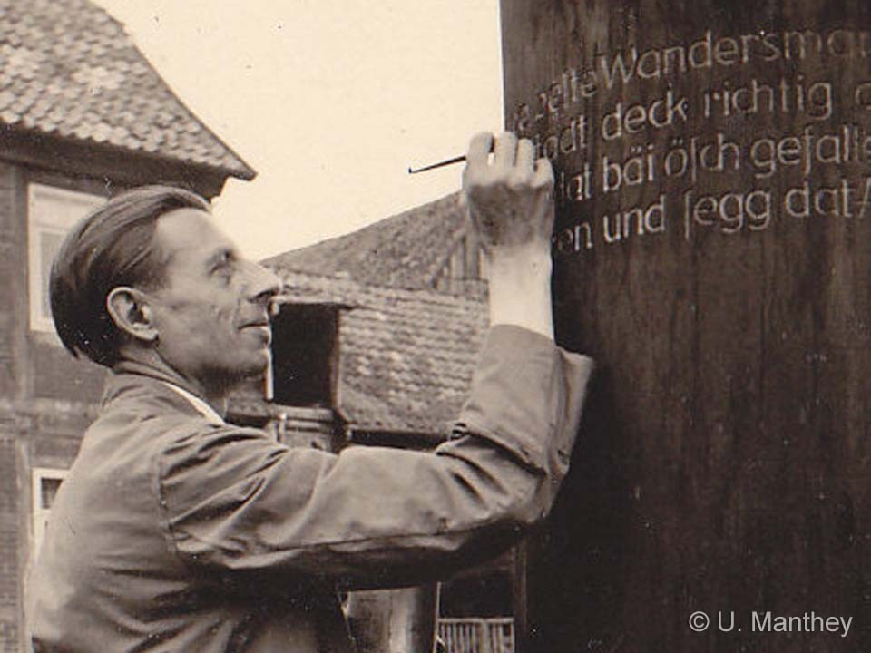 Before the official opening the wooden sculptor puts the last hand to the signpost inscription.